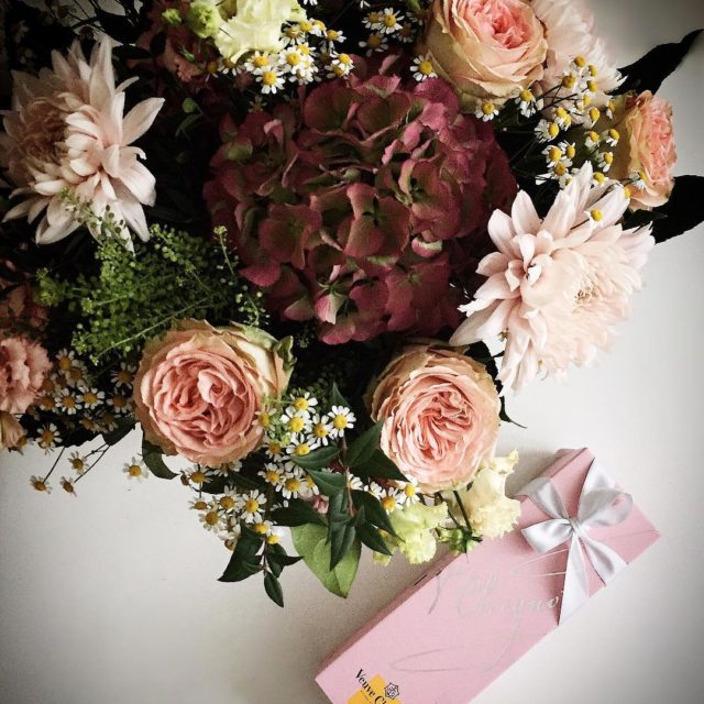 A bouquet of flowers and a bottle of veuveclicquot roshellip